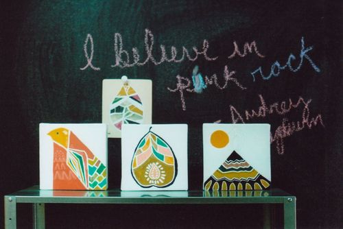 Paintings_on_shelf_against_blackboard